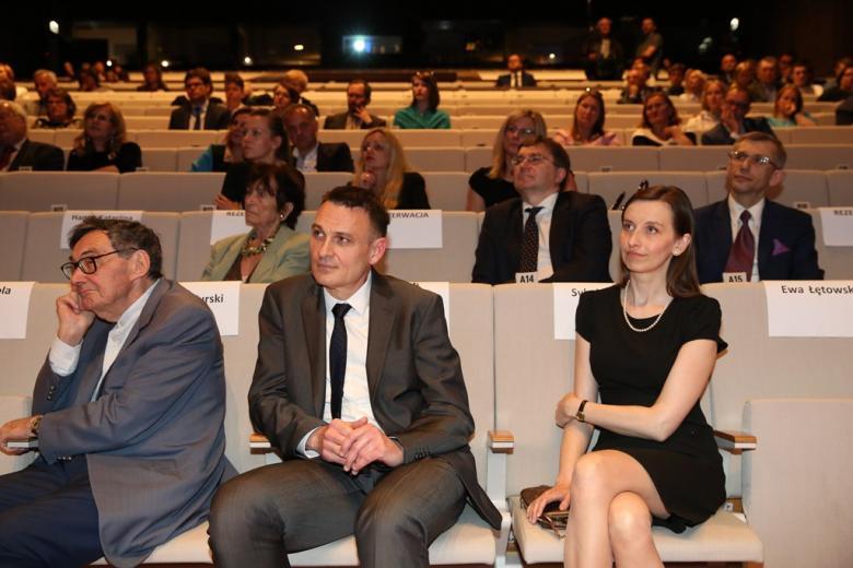 zdjęcie: widownia, na pierwszym planie siedzą dwaj mężczyźni i kobieta