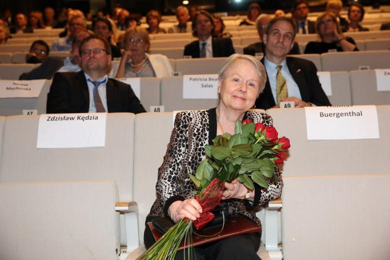 zdjęcie: widownia, na pierwszym planie siedzi kobieta i trzyma bukiet czerwonych kwiatów