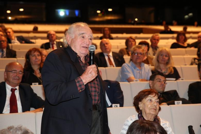 zdjęcie: widownia, na pierwszym planie stoi mężczyzna i mówi do mikrofonu