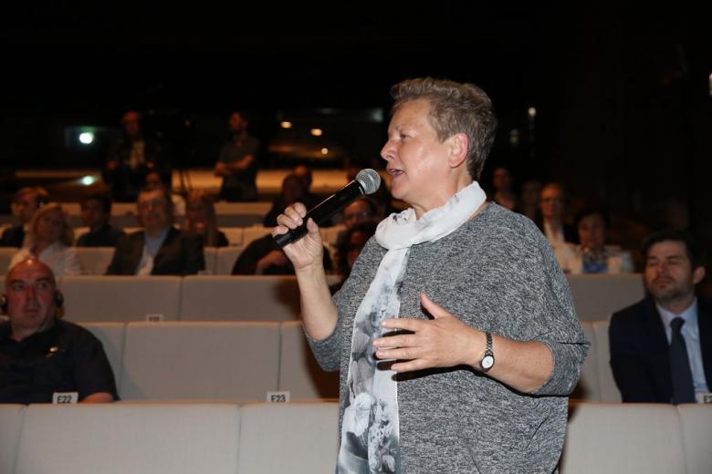 zdjęcie: widownia, na pierwszym planie stoi kobieta i mówi do mikrofonu