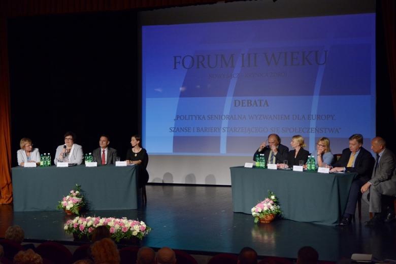 zdjęcie: na schce ustawiono dwa stoły za którymi siedzi osiem osób w tle widać dużu ekran podświetlony na niebiesko