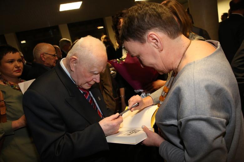Mężczyzna podpisuje książkę