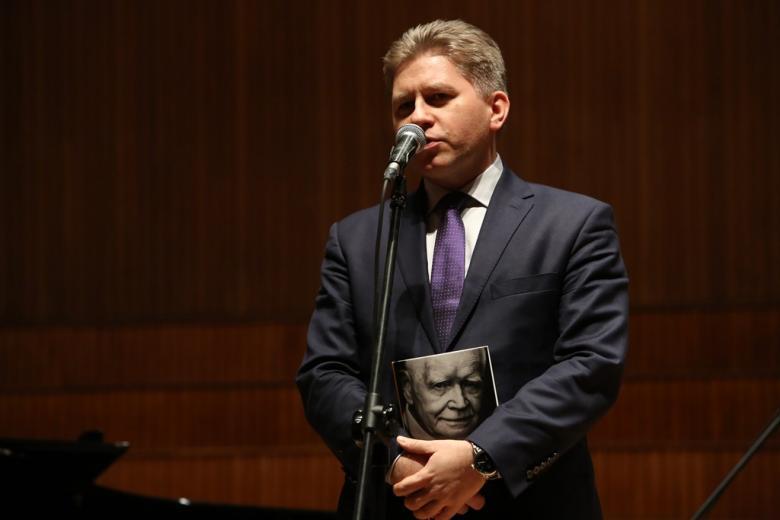Mężczyza na scenie, trzyma książkę, na której okładce jest zdjęcie prof. Strzembosza