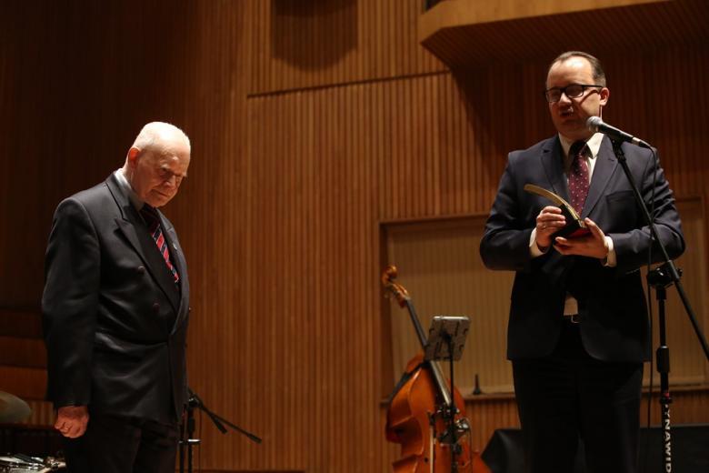 Dwaj mżęczyźni na scenie, jeden trzyma statuetkę nagrody im Włodkowica
