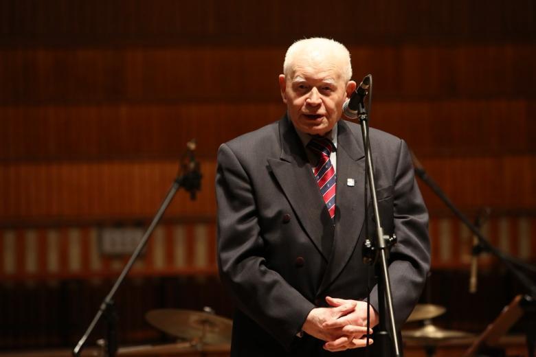 Mężczyzna na scenie przy mikrofonie