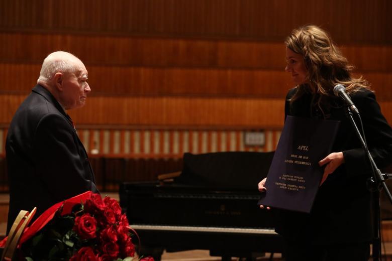 """Mężczyzna i kobieta stoją na scenie. Kobieta pokazuje dokument z tytułem """"Apel prof. Adama Strzembosza..."""" w ciemnej okładce"""