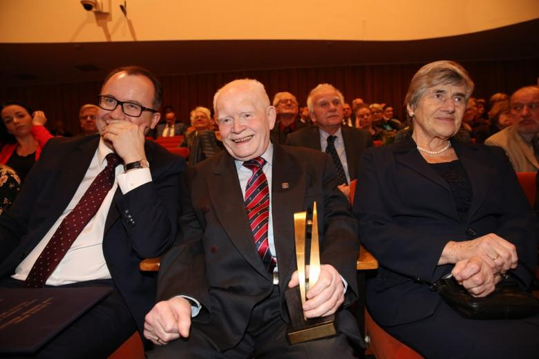 Dwaj mężczyźni i kobieta siedzą na widowni. Mężczyzna w środku trzyma statuetkę nagrody