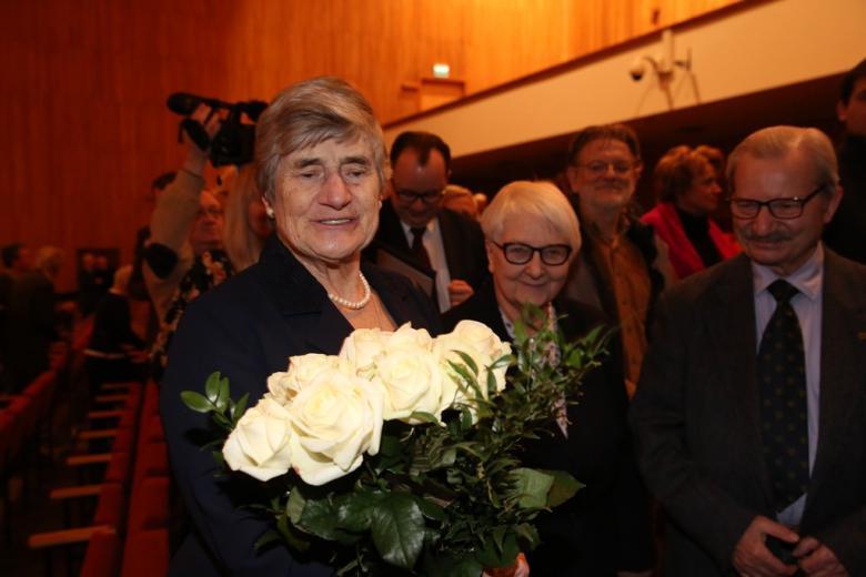 Uśmiechnięta kobieta trzyma bukiet bialych róż
