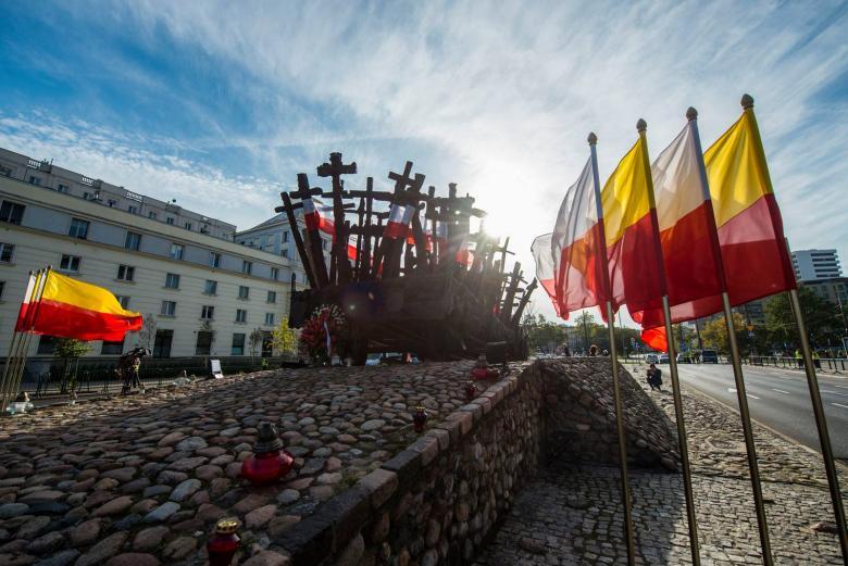 zdjęcie: pomnik przedstawiający wagon kolejowy z krzyżami, przed nim stoją flagi - Polski i Warszawy