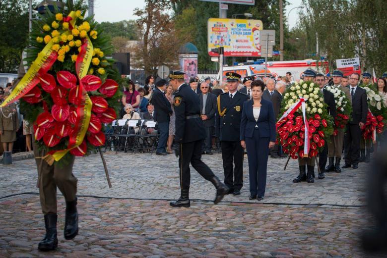 zdjęcie: na pierwszym planie widać mężczyzn w mundurach składających wiązanki z kwiatów, w tle kolejka osób z wieńcami