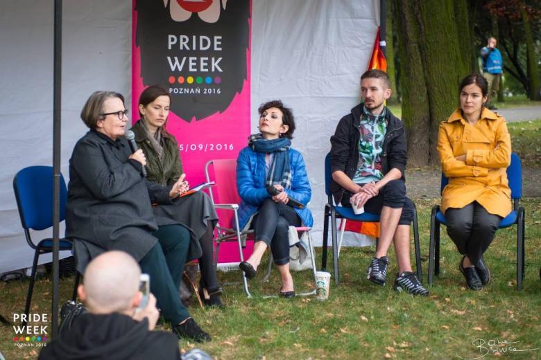 zdjęcie: na pikniku pod białym namiotem siedzi kilka osób