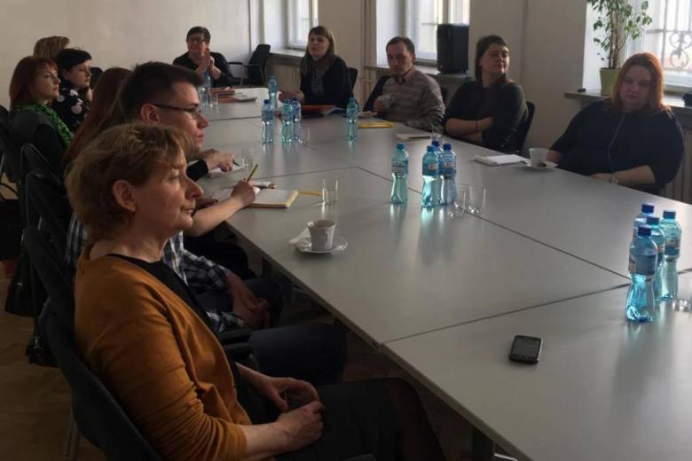zdjęcie: przy złączonych białych stołach siedzi kilkanaście osób