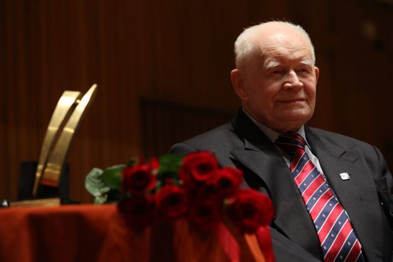 Starszy mężczyzna siedzi przy stole, na którym leży bukiet czerwonych róż i statuetka
