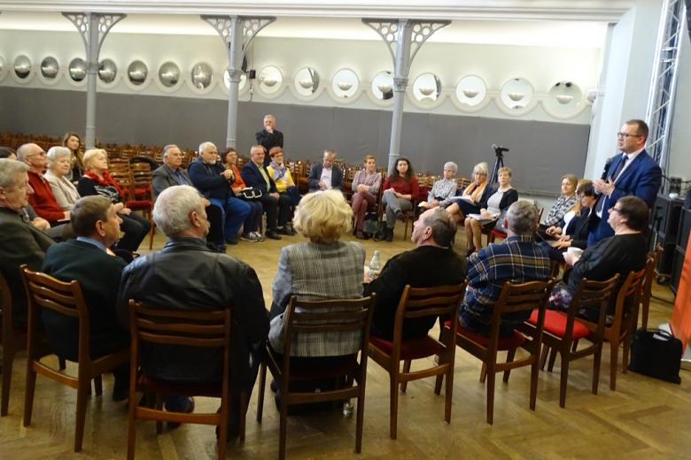 Ludzie siedzą w kręgu na sali widowiskowej