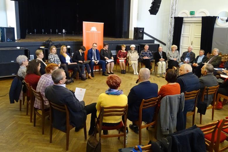 Ludzie siedzą w kręgu, w tle pomarańczowe logo RPO