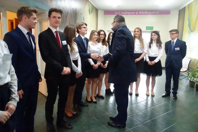 """Uczniowie witają RPO. Na ścianie napis"""" II LO najlepsze w Wielkopolsce"""