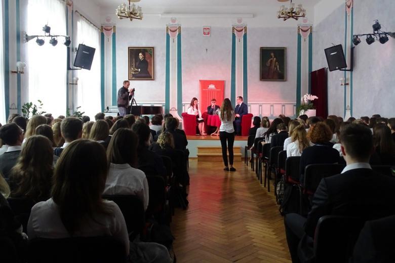 Aula szkolna, na podium uczniowie i Adam Bodnar