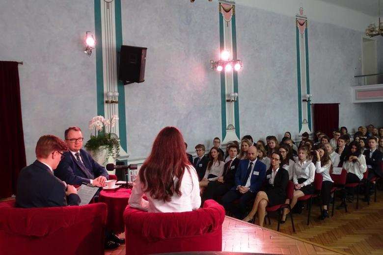 Paneliści na scenie, widok na publiczność - uczniów w strojach galowych