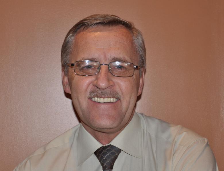 uśmiechnięty siwy mężczyzna w okularach na tle brązowej ściany