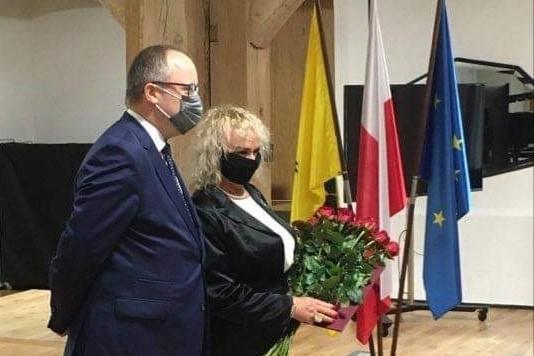 mężczyzna i kobieta, oboje w maseczkach pozują do zdjecia, kobieta trzyma kwiaty