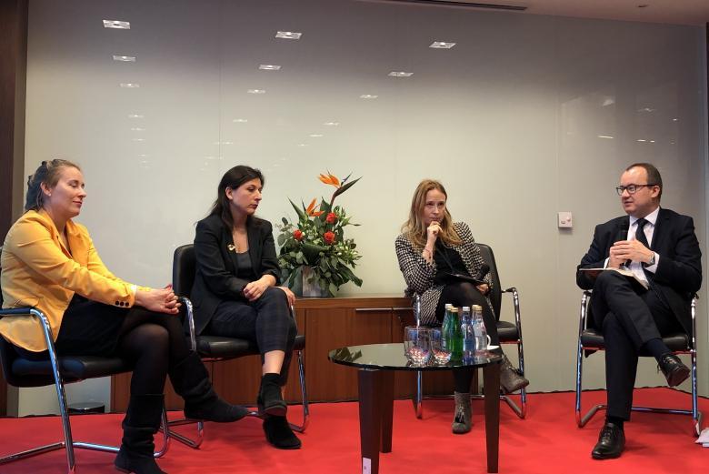 Trzy kobiety i mężczyzna w garniturze prowadzą dyskusję na scenie