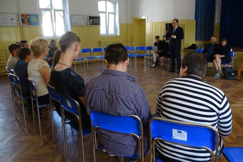 Młodzi ludzie siedzą na sali, mężczyzna stoi