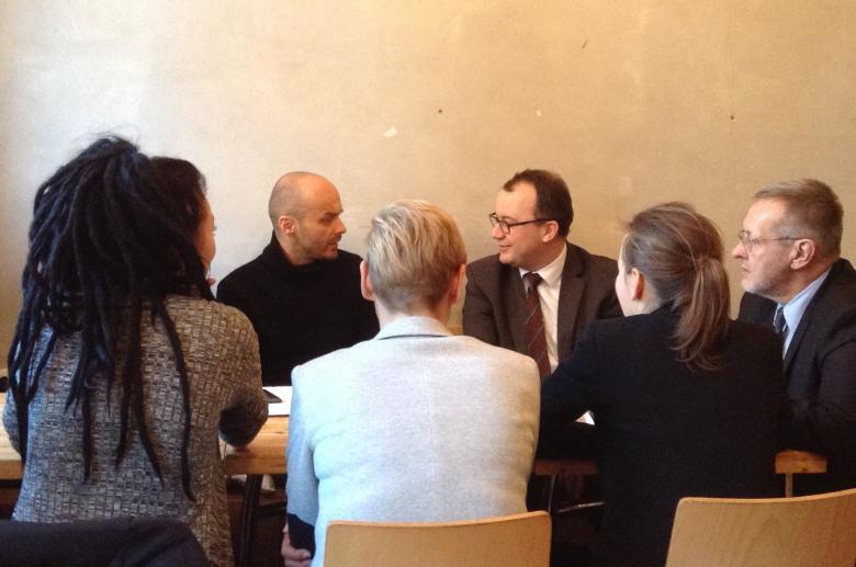 Zdjęcie: rzecznik Bodnar i Marek Piekarski zwróceni do siebie twarzami siedzą przy stola razem z czterema innymi osobami