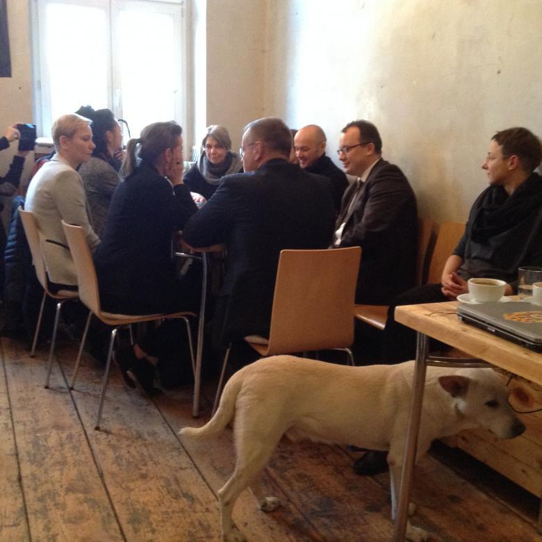 Zdjęcie: rozmowa przy stole, a na pierwszym planie - biały pies
