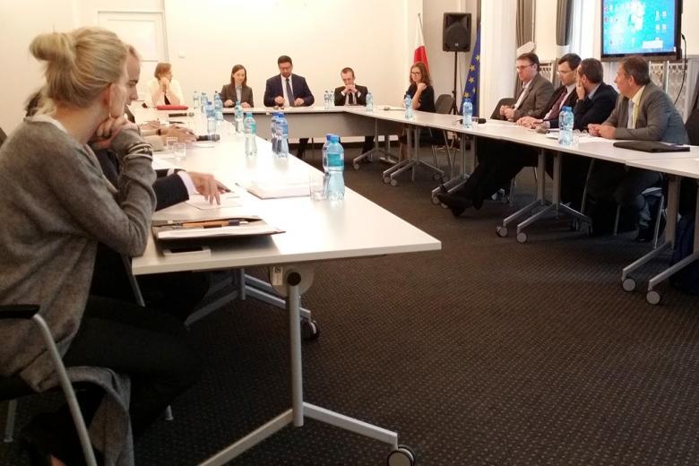 zdjęcie: kilkanaście osób siedzi przy stołach ustawionych w kształcie podkowy