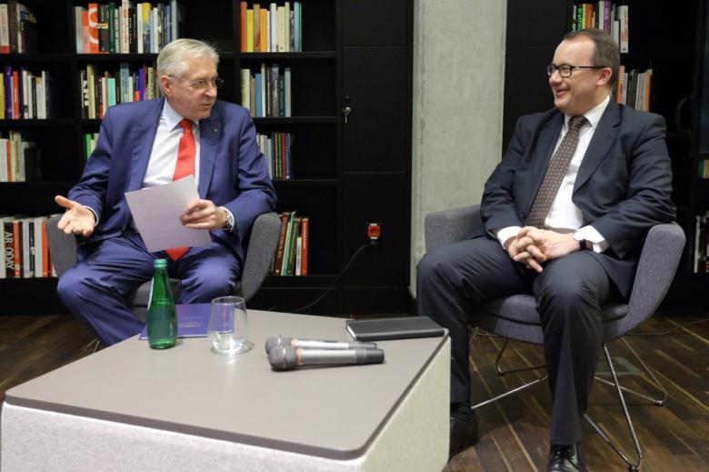 zdjęcie: dwóch mężczyzn w garniturach siedzi przy małym stoliku