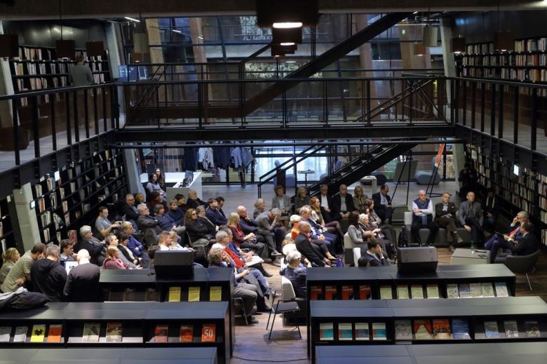 zdjęcie: ujęcie z góry, na dole pośród regałów z książkami siedzi kilkanaście osób