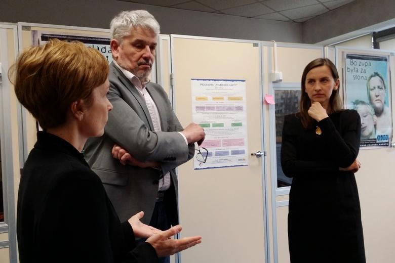 zdjęcie: dwie kobiety i mężczyzna stoją w pomieszczeniu, za nimi kabiny do rozmów