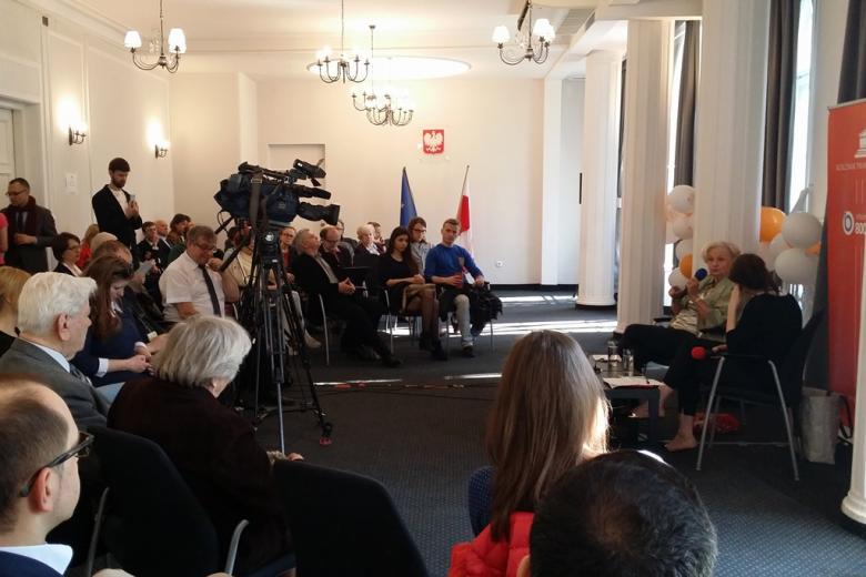 zdjęcie: kilkadziesiąt osób siedzi na sali konferencyjnej, dwie kobiety siedzą po prawej stronie