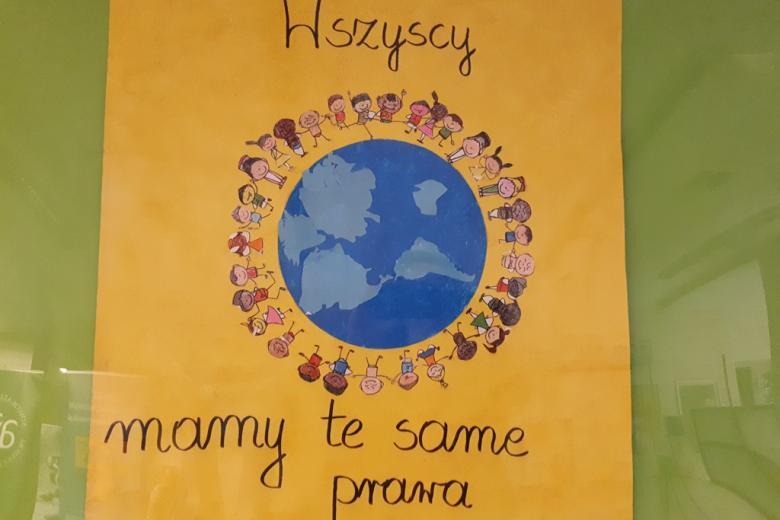zdjęcie: na środku plakatu narysowana Ziemia wokółktórej stoją ludzie trzymający się za ręce. Obok napis: Wszyscy mamy te same prawa.