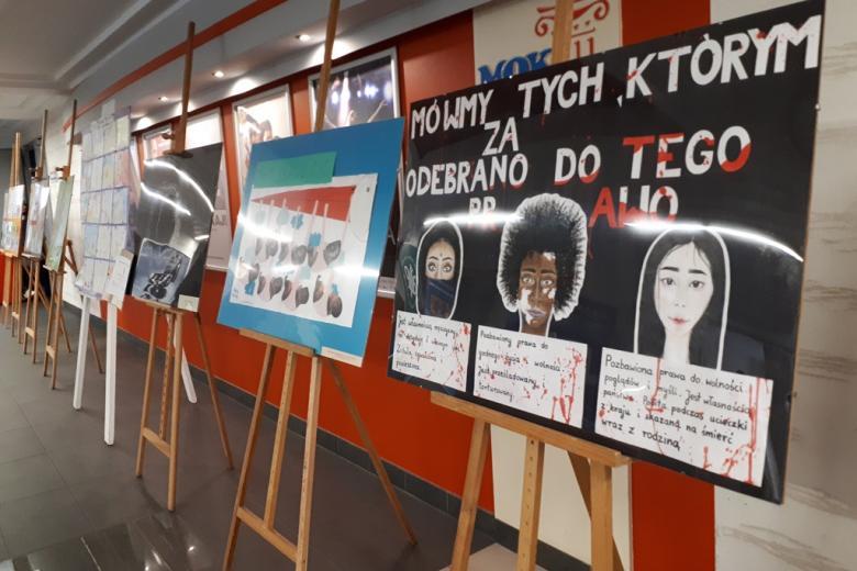 zdjęcie: na korytarzu stoją sztalugi z plakatami wykonanymi przez uczniów