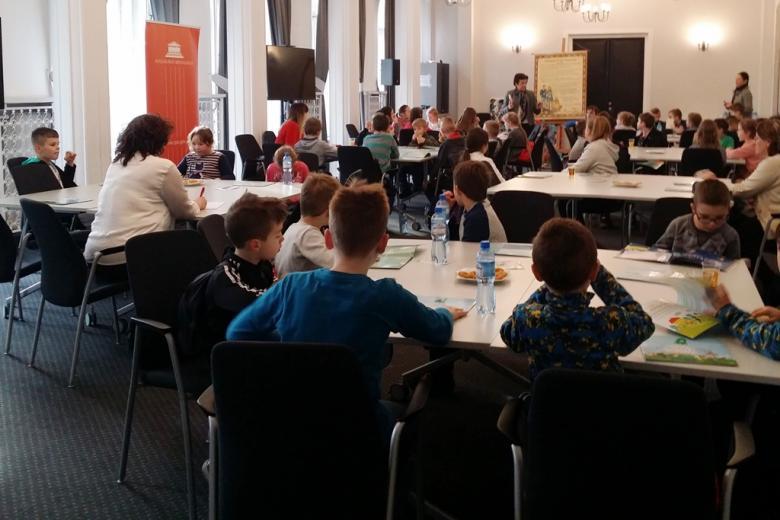 zdjęcie: kilkanaście młodych osób siedzi przy stołach