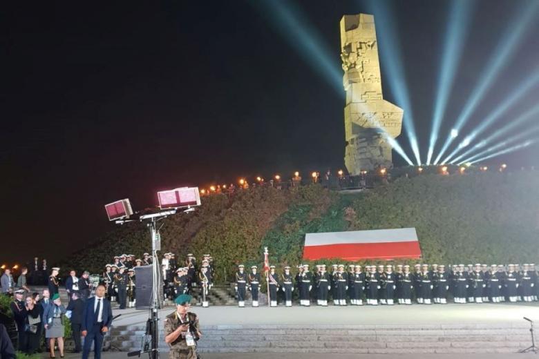 Oświetlony pomnik, pod pomnikiem duża flaga Polski oraz ustawieni w rzędach żołnierze marynarki wojennej