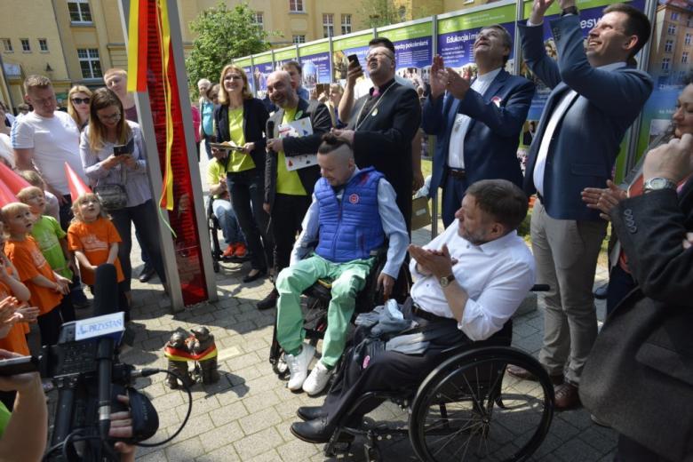 Ludzie zgromadzeni wokół kolorowo ubranego mężczyzny na wózku