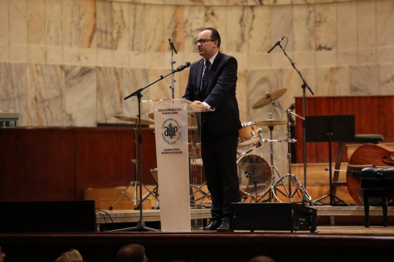 zdjęcie: mężczyzna stoi na scenie przy mównicy