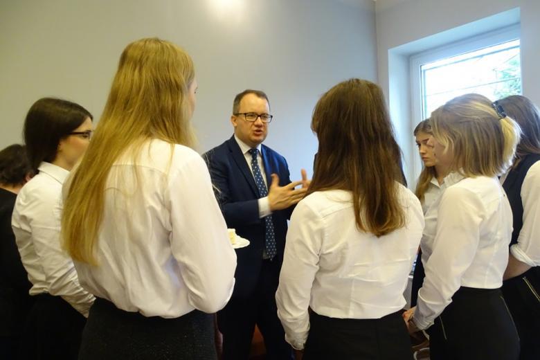 Mężczyzna rozmawia z ucziami w strojach galowych