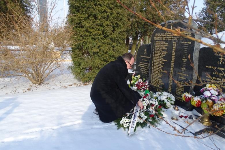 Mężczyzna  kładzie wieniec przed kamieniem z tablicą