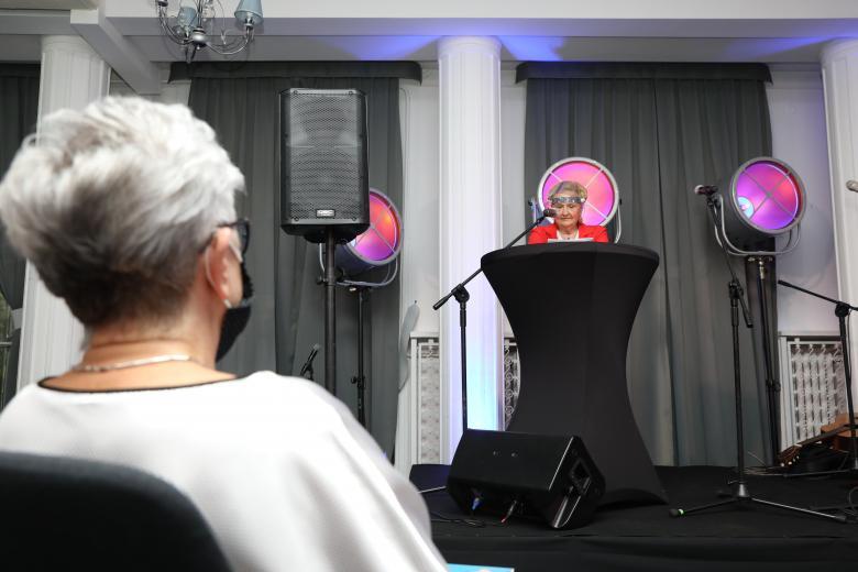 kobiety: jedna na mównicy, a druga jej słucha