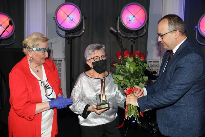 Mężczyzna i kobieta wręczają bukiet kwiatów laureatce nagrody