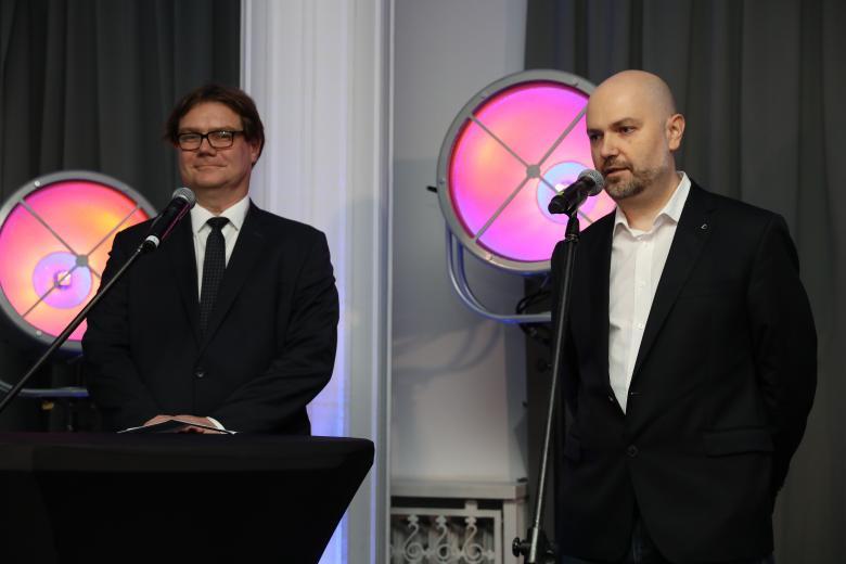 dwaj mężczyźni w garniturach na mównicy
