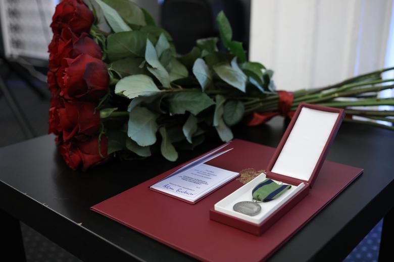 Bukiet czerwonych róż oraz dyplom i odznaka honorowa leżą na eleganckim stole