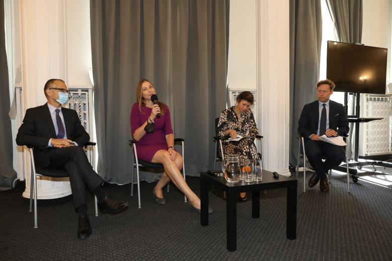 Dwóch mężczyzn i dwie kobiety siedzą i prowadzą dyskusję