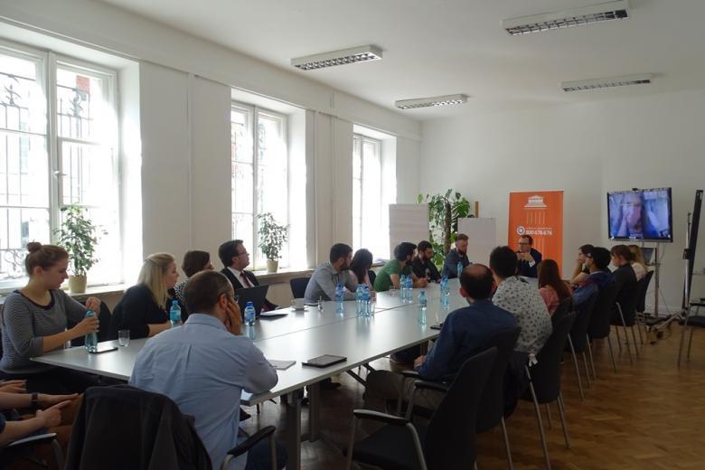 Zdjęcie: widok sali z dużym stołem, wokół którego siedzą ludzie