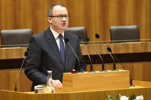 zdjęcie: mężczyzna w garniturze przemawia stojąc za mównicą