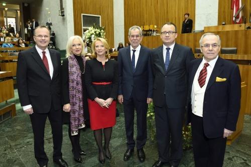 od lewej mężczyzna, przy nim dwie kobiety, obok nich trzech mężczyzn, za nim jest mównica