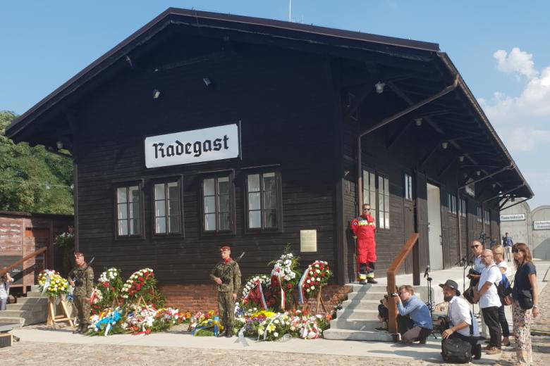 drewniany budynek dawnej stacji kolejowej z wieńcami kwiatów